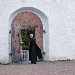 Duhovnik pred vrati samostana (photo: Pixabay)